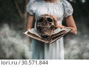 Купить «Female victim holds book and human skull in hand», фото № 30571844, снято 13 мая 2018 г. (c) Tryapitsyn Sergiy / Фотобанк Лори