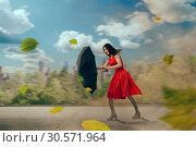 Купить «Woman in red dress with umbrella, hurricane», фото № 30571964, снято 24 мая 2018 г. (c) Tryapitsyn Sergiy / Фотобанк Лори