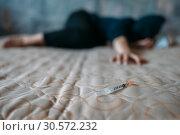 Купить «Female druggy with syringe in hand lies in bed», фото № 30572232, снято 2 июня 2018 г. (c) Tryapitsyn Sergiy / Фотобанк Лори