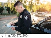 Купить «Male police officers writes a fine on the road», фото № 30572300, снято 6 июня 2018 г. (c) Tryapitsyn Sergiy / Фотобанк Лори
