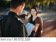 Купить «Police officers reads law to female driver», фото № 30572320, снято 6 июня 2018 г. (c) Tryapitsyn Sergiy / Фотобанк Лори