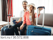 Купить «Happy couple with suitcases prepares for vacation», фото № 30572808, снято 30 июня 2018 г. (c) Tryapitsyn Sergiy / Фотобанк Лори