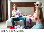 Купить «Playful couple prepares baggage, fees on journey», фото № 30572816, снято 30 июня 2018 г. (c) Tryapitsyn Sergiy / Фотобанк Лори