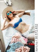 Купить «Woman lies in swimsuit and sunglasses, top view», фото № 30572832, снято 30 июня 2018 г. (c) Tryapitsyn Sergiy / Фотобанк Лори