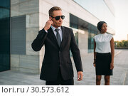 Bodyguard in sunglasses and black business woman. Стоковое фото, фотограф Tryapitsyn Sergiy / Фотобанк Лори