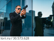 Купить «Bodyguard with security earpiece and gun in hands», фото № 30573628, снято 8 августа 2018 г. (c) Tryapitsyn Sergiy / Фотобанк Лори