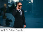 Male bodyguard uses security earpiece outdoors. Стоковое фото, фотограф Tryapitsyn Sergiy / Фотобанк Лори