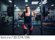 Купить «Muscular athlete poses at the stand with barbell», фото № 30574196, снято 4 сентября 2018 г. (c) Tryapitsyn Sergiy / Фотобанк Лори