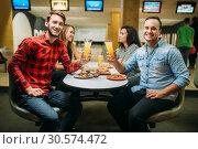 Friends drinks and eats pizza in bowling club. Стоковое фото, фотограф Tryapitsyn Sergiy / Фотобанк Лори
