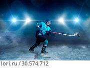 Купить «Hockey player with stick and puck makes a throw», фото № 30574712, снято 20 апреля 2017 г. (c) Tryapitsyn Sergiy / Фотобанк Лори