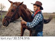 Купить «Cowboy poses with horse on texas ranch, wild west», фото № 30574916, снято 20 октября 2018 г. (c) Tryapitsyn Sergiy / Фотобанк Лори