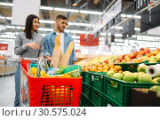 Couple with cart in supermarket, fruits department. Стоковое фото, фотограф Tryapitsyn Sergiy / Фотобанк Лори