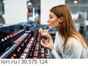 Female customer testing lip liner in make-up shop. Стоковое фото, фотограф Tryapitsyn Sergiy / Фотобанк Лори
