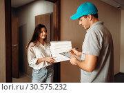 Купить «Female customer signs order, pizza delivery», фото № 30575232, снято 4 ноября 2018 г. (c) Tryapitsyn Sergiy / Фотобанк Лори