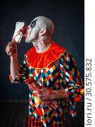 Купить «Scary bloody clown licks the knife blade», фото № 30575832, снято 7 декабря 2018 г. (c) Tryapitsyn Sergiy / Фотобанк Лори