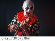 Купить «Bloody clown holds human hand, finger in his teeth», фото № 30575868, снято 7 декабря 2018 г. (c) Tryapitsyn Sergiy / Фотобанк Лори