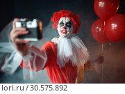 Купить «Scary bloody clown with crazy eyes makes selfie», фото № 30575892, снято 7 декабря 2018 г. (c) Tryapitsyn Sergiy / Фотобанк Лори