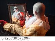 Купить «Bloody clown with crazy eyes sitting at the mirror», фото № 30575904, снято 7 декабря 2018 г. (c) Tryapitsyn Sergiy / Фотобанк Лори