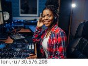 Купить «Female musician in headphones in recording studio», фото № 30576208, снято 22 декабря 2018 г. (c) Tryapitsyn Sergiy / Фотобанк Лори