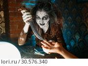 Купить «Scary witch with knife, spiritual seance», фото № 30576340, снято 29 января 2019 г. (c) Tryapitsyn Sergiy / Фотобанк Лори