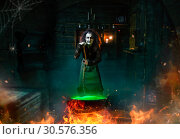 Scary witch cooking potions and reads the spell. Стоковое фото, фотограф Tryapitsyn Sergiy / Фотобанк Лори