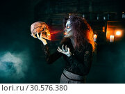 Scary witch holds human skull and reads the spell. Стоковое фото, фотограф Tryapitsyn Sergiy / Фотобанк Лори