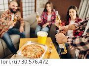 Купить «Friends raise a toast with beer at the home party», фото № 30576472, снято 3 февраля 2019 г. (c) Tryapitsyn Sergiy / Фотобанк Лори