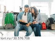 Купить «Couple with luggage waiting for departure, airport», фото № 30576708, снято 17 февраля 2019 г. (c) Tryapitsyn Sergiy / Фотобанк Лори