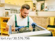 Worker in uniform repairs refrigerator compressor. Стоковое фото, фотограф Tryapitsyn Sergiy / Фотобанк Лори