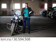 Беременная женщина, стоящая рядом с мотоциклом, держит белый открытый шлем, парковка. Стоковое фото, фотограф Кекяляйнен Андрей / Фотобанк Лори