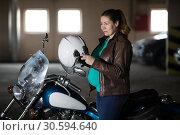 Купить «Motorcyclist pregnant woman preparing to ride chopper bike, put on her helmet at parking lot», фото № 30594640, снято 24 февраля 2019 г. (c) Кекяляйнен Андрей / Фотобанк Лори