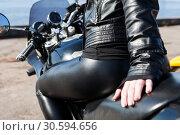 Купить «Female motorcyclist dressed black leather outfit and leggins sitting on bike seat, looking behind, view at booty ass», фото № 30594656, снято 6 апреля 2019 г. (c) Кекяляйнен Андрей / Фотобанк Лори