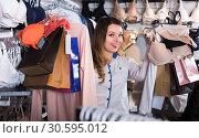 Купить «female customer showing her purchases in underwear shop», фото № 30595012, снято 20 марта 2017 г. (c) Яков Филимонов / Фотобанк Лори