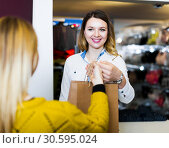 Купить «Woman seller giving diverse purchases to customer», фото № 30595024, снято 20 марта 2017 г. (c) Яков Филимонов / Фотобанк Лори
