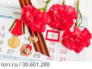 Купить «9 May - medals of Great patriotic war with red carnations and George ribbon lying on the calendar with 9 May date», фото № 30601288, снято 8 апреля 2017 г. (c) Зезелина Марина / Фотобанк Лори