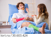 Купить «Loving wife looking after injured husband in hospital», фото № 30603424, снято 24 сентября 2018 г. (c) Elnur / Фотобанк Лори