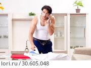 Купить «Young man ironing in the bedroom», фото № 30605048, снято 29 ноября 2018 г. (c) Elnur / Фотобанк Лори