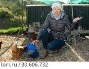 Купить «Young woman farmer caring for poultry», фото № 30606732, снято 18 марта 2019 г. (c) Яков Филимонов / Фотобанк Лори
