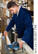 Купить «male worker processing plank in machine at workshop», фото № 30607104, снято 7 ноября 2016 г. (c) Яков Филимонов / Фотобанк Лори