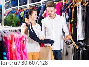 Купить «Glad couple deciding on new sportswear», фото № 30607128, снято 22 ноября 2016 г. (c) Яков Филимонов / Фотобанк Лори
