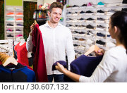 Купить «Smiling loving couple deciding on new sportswear», фото № 30607132, снято 22 ноября 2016 г. (c) Яков Филимонов / Фотобанк Лори