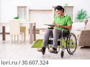Купить «Young handsome man in wheelchair at home», фото № 30607324, снято 14 ноября 2018 г. (c) Elnur / Фотобанк Лори