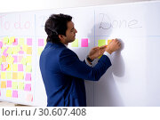 Купить «Young handsome employee in front of whiteboard with to-do list», фото № 30607408, снято 16 октября 2018 г. (c) Elnur / Фотобанк Лори