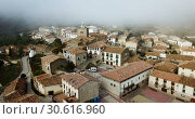 Купить «View from drone of roofs of houses in traditional village of Liedena in foggy morning, Navarre, Spain», видеоролик № 30616960, снято 23 декабря 2018 г. (c) Яков Филимонов / Фотобанк Лори