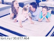 Купить «Small client with his happy family choosing right mattress in home furnishings store», фото № 30617464, снято 26 июня 2017 г. (c) Яков Филимонов / Фотобанк Лори