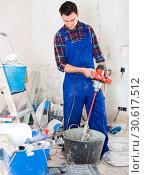 Купить «professional builder mixing plaster in bucket using electric mixer», фото № 30617512, снято 21 мая 2017 г. (c) Яков Филимонов / Фотобанк Лори