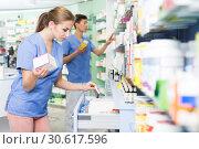 Купить «Female pharmacist looking different medicines at shelves in apothecary», фото № 30617596, снято 26 марта 2018 г. (c) Яков Филимонов / Фотобанк Лори