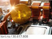 Купить «Golden physycal bitcoin near the computer components. Business concept of digital cryptocurrency», фото № 30617808, снято 4 апреля 2019 г. (c) Зезелина Марина / Фотобанк Лори