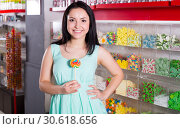 Smiling girl sucking lollypop in store. Стоковое фото, фотограф Яков Филимонов / Фотобанк Лори