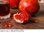 Red pomegranate fruits and glass with juice on a dark surface. Стоковое фото, фотограф Евгений Харитонов / Фотобанк Лори